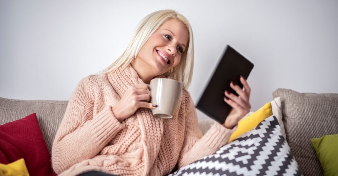 Blonde woman sitting on the sofa inside her new home and holding a cup while watching multimedia content on digital tablet.
